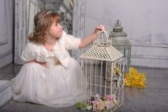 Ma?a dziewczynka z biel sukni? blisko kom?rki z kwiatami zdjęcie royalty free