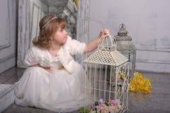 Ma?a dziewczynka z biel sukni? blisko kom?rki z kwiatami zdjęcia stock