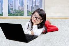 Mała dziewczynka z laptopem na dywanie Fotografia Stock