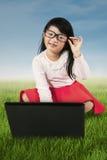 Mała dziewczynka z laptopem przy polem Fotografia Stock