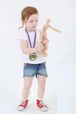 Mała dziewczynka z medalem na klatce piersiowej stoi drewnianej atrapy i trzyma Obrazy Royalty Free