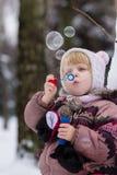Mała dziewczynka z mydlanymi bubles w zimie obraz stock