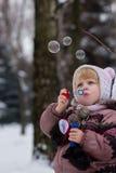 Mała dziewczynka z mydlanymi bubles w zimie fotografia royalty free