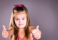Mała dziewczynka z niebieskimi oczami pokazuje aprobaty Zdjęcia Royalty Free