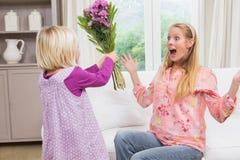 Mała dziewczynka zaskakuje jej matki z kwiatami Zdjęcie Royalty Free
