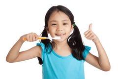 Małe azjatykcie dziewczyn aprobaty z toothbrush Fotografia Royalty Free