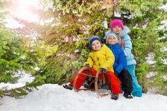 Małe dzieci i zimy zabawa na saneczki w parku Zdjęcie Royalty Free