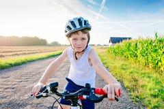 Ma?e dziecko ch?opiec jedzie jego bicykl w bia?ym he?mie obrazy royalty free