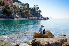 Ma?e dziecko ch?opiec pi?cie na kamieniach na pla?y morze ?r?dziemnomorskie w Liguria regionie, W?ochy Wspania?y krajobraz Zoagli obrazy stock
