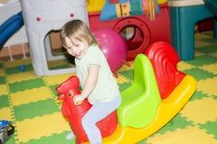 Małe dziecko w dziecka ` s pokoju Rozrywki centrum i dziecka ` s gry Niegrzeczna zabawa w dziecka ` s pokoju Fotografia Stock