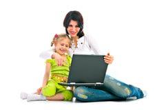 MA e figlia con il computer portatile Fotografia Stock