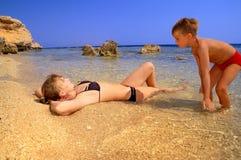 MA e figlio sulla spiaggia sul cielo blu della priorità bassa Immagini Stock