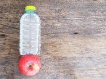 Maçã e garrafa vermelhas da água Fotografia de Stock