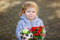 Ma?ego berbecia urocza dziewczyna z czerwonymi i bia?ymi ranunculus kwiatami w wiosna ogr?dzie Szcz??liwy ?liczny dziecko trzyma  zdjęcie royalty free