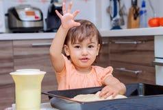 Małej dziewczynki kulinarny jedzenie w kuchni Zdjęcie Stock