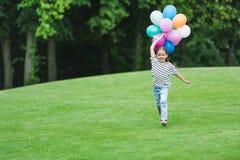 Małej dziewczynki mienia bieg w parku i balony Zdjęcia Royalty Free