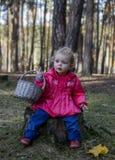 Małej dziewczynki obsiadanie na fiszorku w drewnach z koszem Zdjęcie Stock