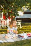 Małej dziewczynki obsiadanie na zielonej trawie Zdjęcie Royalty Free