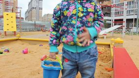 Ma?ej dziewczynki obsiadanie w piaskownicie i bawi? si? z foremkami na boisku zbiory wideo