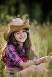 Małej dziewczynki obsiadanie w polu jest ubranym kowbojskiego kapelusz Zdjęcie Royalty Free