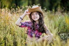 Małej dziewczynki obsiadanie w polu jest ubranym kowbojskiego kapelusz Fotografia Royalty Free