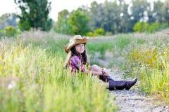 Małej dziewczynki obsiadanie w polu jest ubranym kowbojskiego kapelusz Fotografia Stock