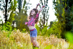Małej dziewczynki obsiadanie w polu jest ubranym kowbojskiego kapelusz Obraz Stock