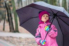 Małej dziewczynki odprowadzenie pod parasolem w miasto parku Zdjęcie Stock