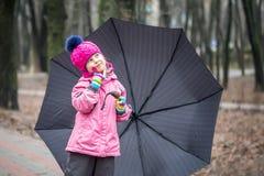 Małej dziewczynki odprowadzenie pod parasolem w parku Zdjęcia Stock