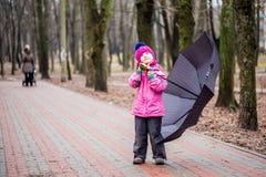 Małej dziewczynki odprowadzenie pod parasolem w parku Obraz Stock