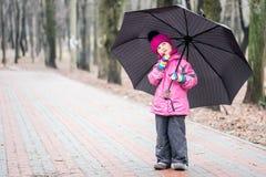 Małej dziewczynki odprowadzenie pod parasolem w parku Fotografia Stock