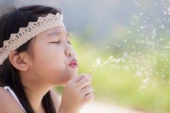 Małej dziewczynki podmuchowy dandelion Zdjęcia Royalty Free