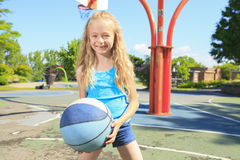 Małej dziewczynki sztuki koszykówka na z boiskiem Fotografia Royalty Free