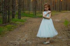 Mała emocjonalna dziewczyna chodzi w lato lesie w sukni Zdjęcia Stock