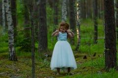 Mała emocjonalna dziewczyna chodzi w lato lesie w sukni Obrazy Stock