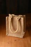 Mała jutowa torba na drewnianym stole Obrazy Stock