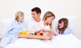 ma kochającego obsiadanie łóżkowa śniadaniowa rodzina obrazy stock