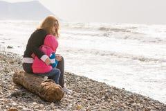 Ma mère et vieille fille de cinq ans s'asseyant sur la plage Image stock