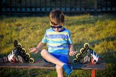 Ma?a przystojna ch?opiec w ostrzach siedzi w ?awce w lato parku zdjęcia stock