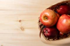 Ma??s vermelhas maduras em uma cesta em um fundo de madeira brilhante fotos de stock royalty free
