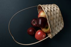 Ma??s vermelhas maduras em uma cesta em um fundo escuro imagens de stock