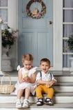 Ma soeur et jeune frère s'asseyant sur les escaliers à la maison et Photos stock
