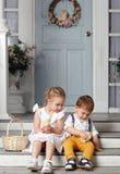 Ma soeur et jeune frère s'asseyant sur les escaliers à la maison et Photo stock