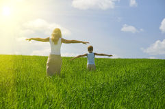 Ma and son. Walk in field. agricultural nature landscape with blue cloud sky and green grass stock photography