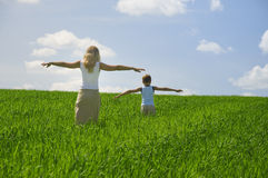 Ma and son walk in field. Agricultural nature landscape with blue cloud sky and green grass stock image