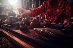 Ma?tre caucasien dans le kimono faisant le th? naturel dans la chambre noire avec un int?rieur en bois Tradition, sant?, harmonie images libres de droits