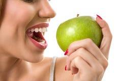 Maçã verde cortante da mulher com dentes cobertos de urzes Foto de Stock Royalty Free