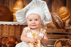 Mały dziecko gotuje croissant w tle kosze z rolkami i chlebem Zdjęcia Royalty Free