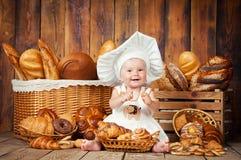 Mały dziecko gotuje croissant w tle kosze z rolkami i chlebem Zdjęcia Stock
