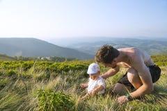 Mały dziecko i jego ojcujemy w górach Obrazy Royalty Free